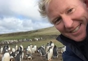 Kevin Millington with penguins in Eastern Caribbean
